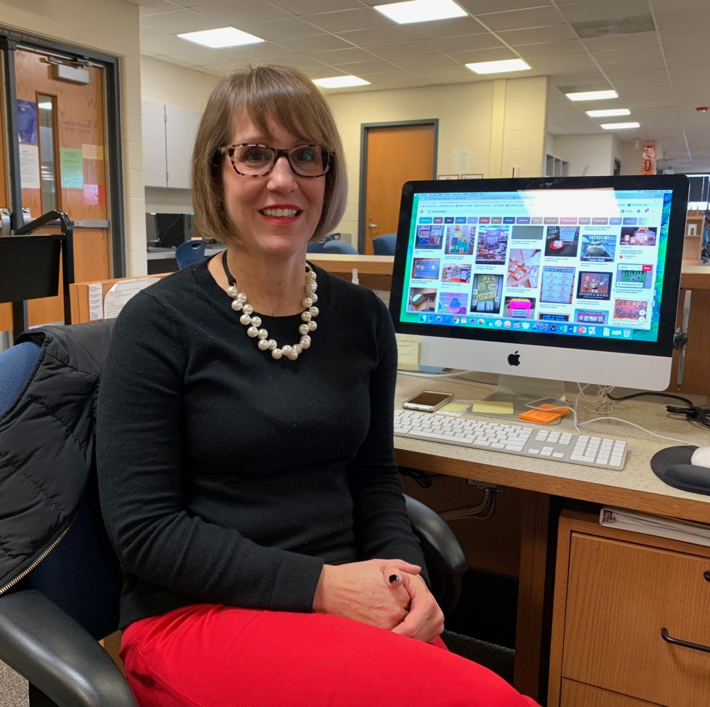 Purely decorative photo of stylish Ms. Gaefke wearing a black shirt and pearls in front of her computer at school.
